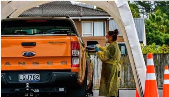 3月23日,在新西兰奥克兰一处检测点,医务人员在进行快速检测。